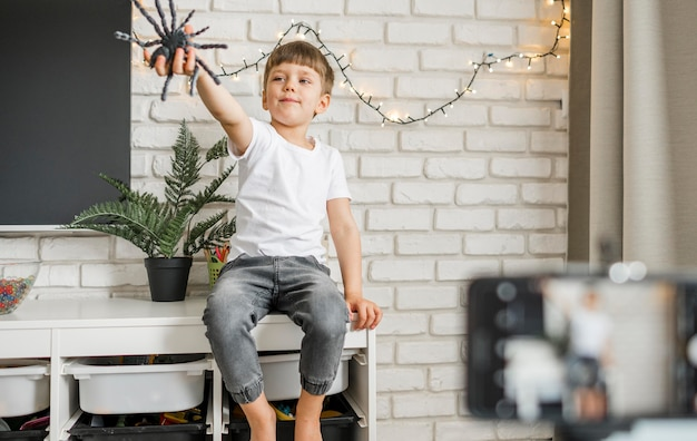 Kleines kind, das mit spinne spielt