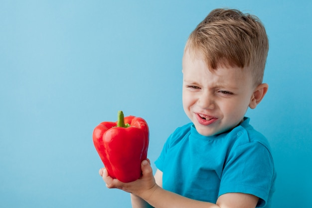 Kleines kind, das pfeffer in seinen händen auf blauer wand hält. veganes und gesundes konzept