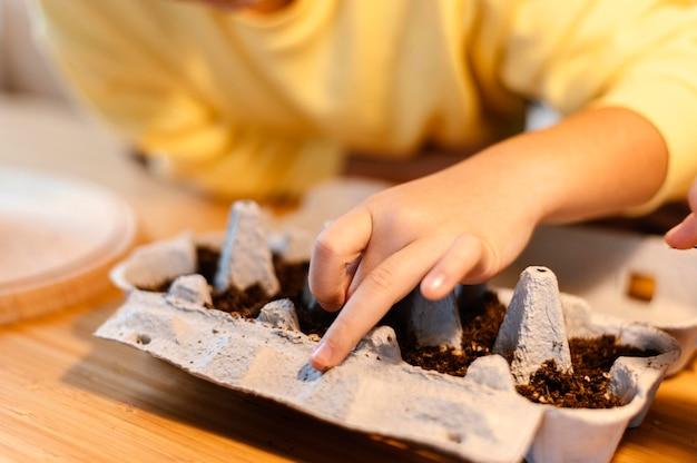 Kleines kind, das samen zu hause pflanzt