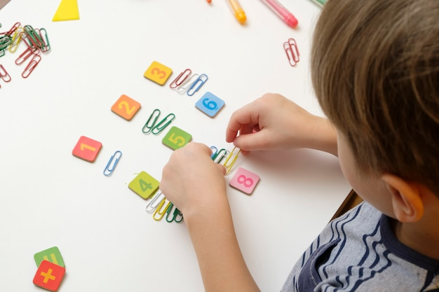 Kleines kind, das sich auf die grundschule vorbereitet, die einfache mathematikübungen macht.
