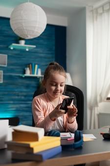 Kleines kind, das smartphone hält und online-geschichte mit virtuellem buch liest