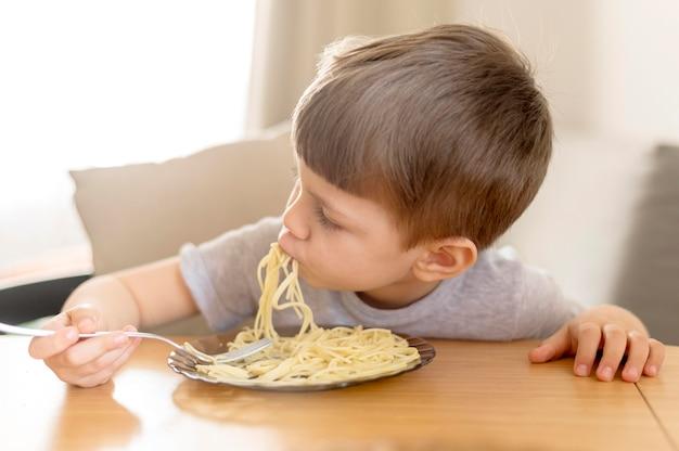 Kleines kind, das spaghetti isst