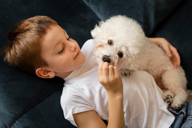 Kleines kind, das spaß mit seinem hund zu hause hat