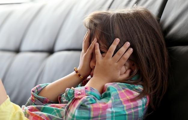Kleines kind, das verstecken spielt und ihre augen schließt