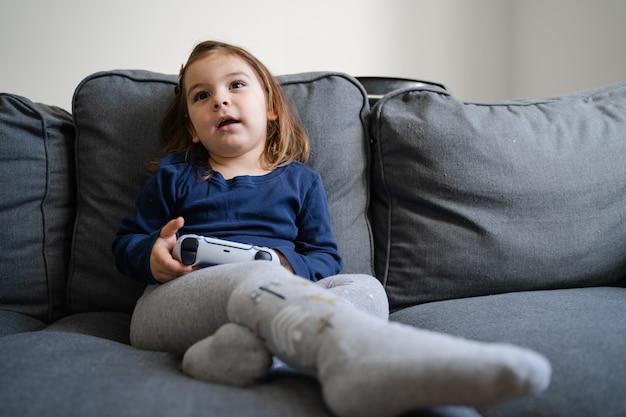 Kleines kind, das videospiele mit gamepad auf konsole spielt
