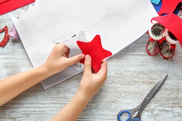Kleines kind, das weihnachtssterne vom filz am tisch hält