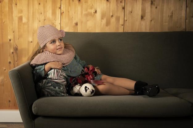 Kleines kind, das winterkleidung trägt und auf einem sofa mit einem kissen gegen eine holzwand liegt