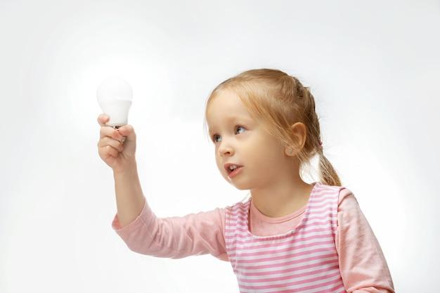 Kleines kind halten glühbirne. bildungskonzept.