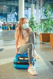 Kleines kind in der medizinischen maske im flughafen, der auf das einsteigen wartet