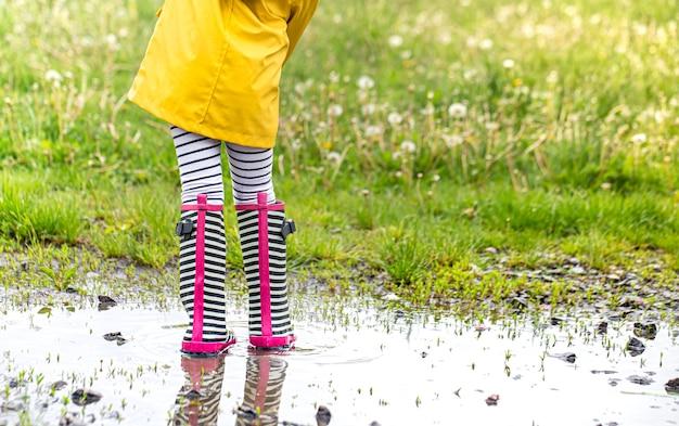Kleines kind in einem leuchtend gelben regenmantel und gestreiften gummistiefeln.