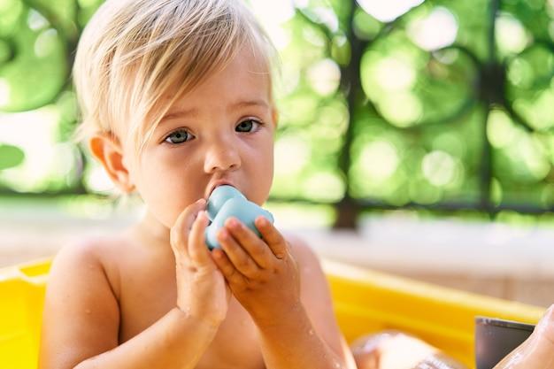 Kleines kind kaut auf einer gummiente