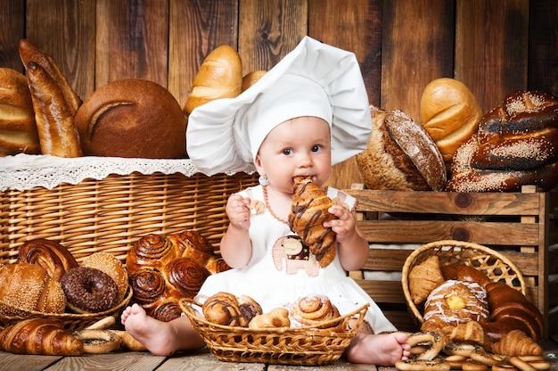 Kleines kind kocht ein croissant in den körben mit brötchen und brot.