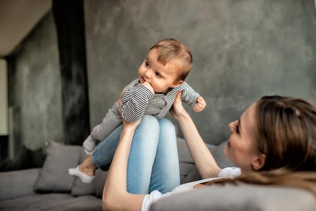 Kleines kind lächelnd und glücklich mit mutter auf dem sofa