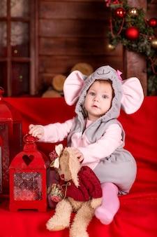 Kleines kind (mädchen) im feiertagskostüm der maus (ratte) sitzt nahe weihnachtsdekorationen