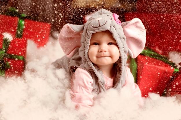 Kleines kind (mädchen) im festlichen anzug der maus (ratte) sitzt im weißen schnee nahe weihnachtsgeschenken