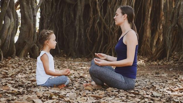 Kleines kind mädchen mit ihrer jungen mutter, die zusammen von angesicht zu angesicht unter großem banyanbaum meditiert