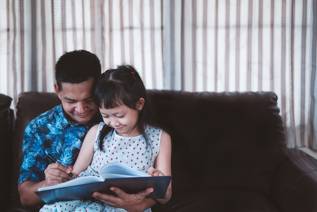 Kleines kind mädchen und vater genießen es, gemeinsam zu hause ein buch zu lesen. soziale distanz während der quarantäne, online-bildungskonzept