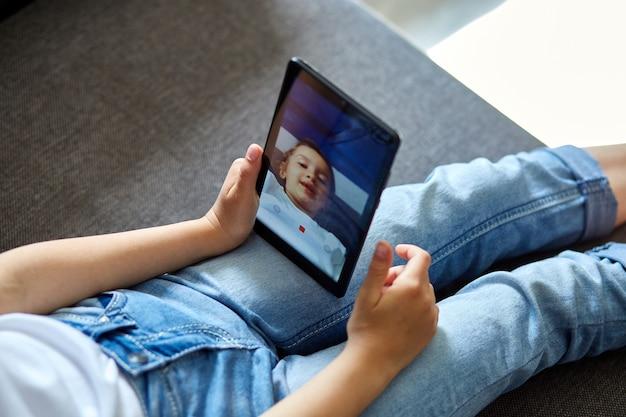 Kleines kind mädchen zu hause sprechen video mit tablet-treffen, online-anruf freund