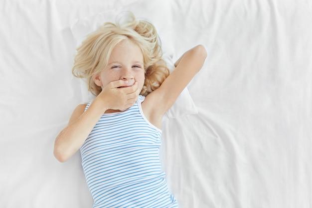 Kleines kind mit blonden haaren, blauen augen und sommersprossiger haut, im bett liegend, den mund mit der hand bedeckend und gähnend. entzückendes kleines mädchen, das am morgen aufwacht und schläfrigen ausdruck nach dem schlaf hat
