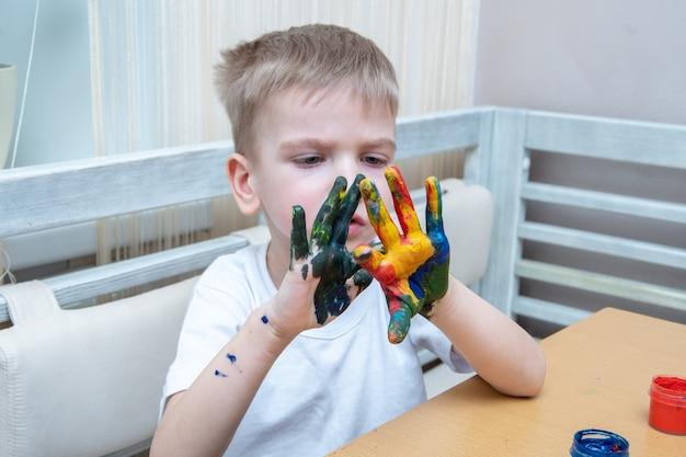 Kleines kind mit bunt bemalten händen. ein konzentrierter junge schmiert sich farbe auf die hände und betrachtet das ergebnis. das kind lernt malen. erlernen der grundlagen der farbe