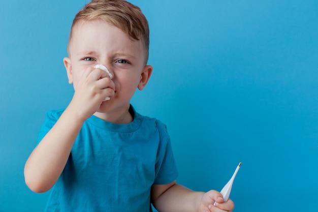 Kleines kind mit einem thermometer, misst die höhe seines fiebers