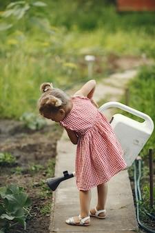 Kleines kind mit einer gießkanne mit blumen gießen. mädchen mit einem trichter. kind in einem rosa kleid.