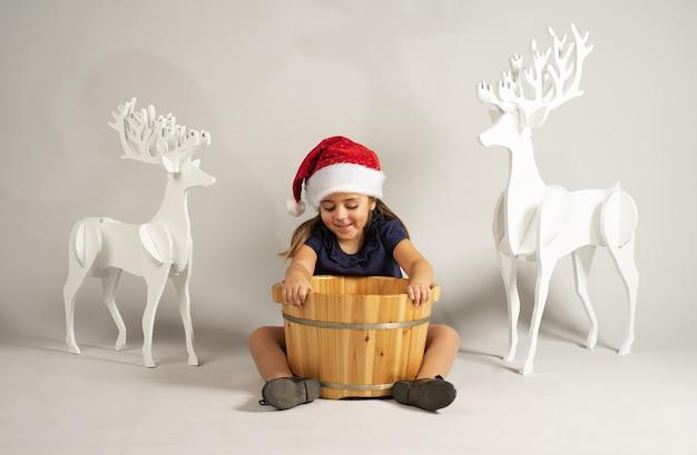 Kleines kind mit einer weihnachtsmütze, die einen hölzernen korb auf dem boden mit hirschdekorationen auf ihm hält