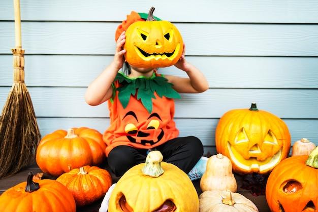 Kleines kind mit halloween-kürbis
