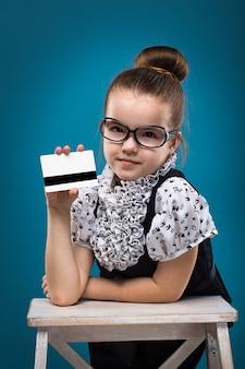 Kleines kind mit kreditkarte gekleidet wie lehrer