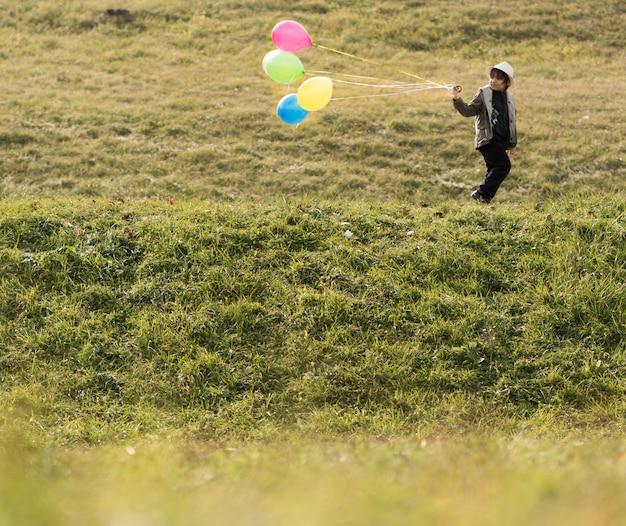 Kleines kind mit luftballons auf der wiese