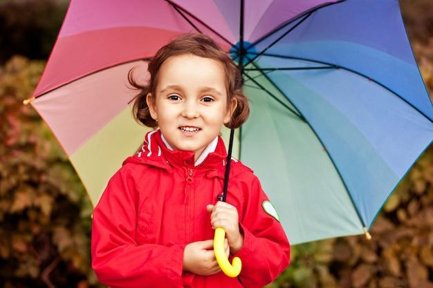 Kleines kind mit mehrfarbigem regenbogenregenschirm draußen.