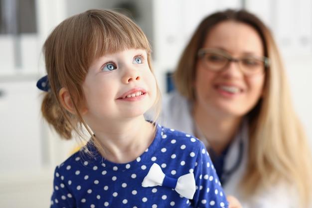 Kleines kind mit mutter am kinderarztempfang. porträtbabyhilfe der körperlichen prüfung nettes säuglingsgesunder lebensstil-bezirk ringsum kinderkrankheitskliniktestqualität und babykonzept