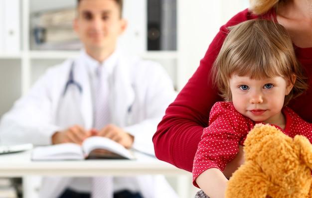 Kleines kind mit mutter am kinderarztempfang