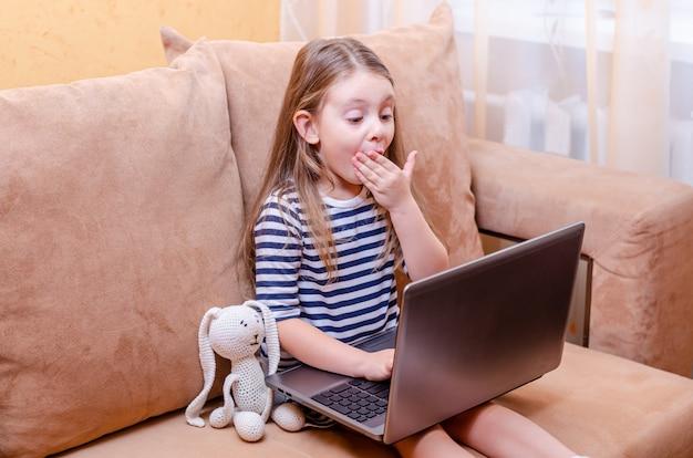 Kleines kind mit netbook und plüschtier