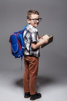Kleines kind mit schultasche und buch. junger schüler mit rucksack und lehrbuch