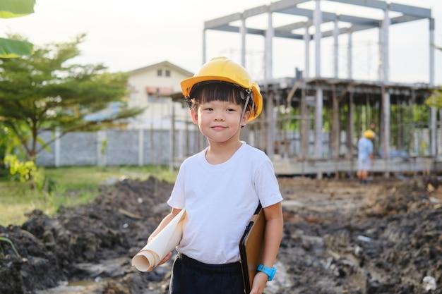 Kleines kind mit schutzhelm, das blaupause und tablet-pc hält, der auf der baustelle steht