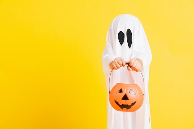 Kleines kind mit weiß gekleidetem kostüm halloween-geist beängstigend er hält orange kürbisgeist zur hand
