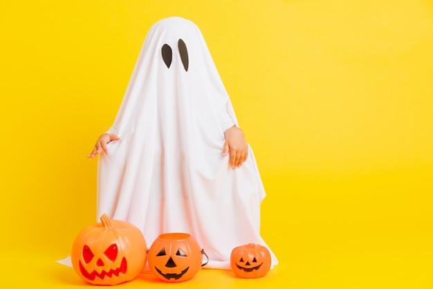 Kleines kind mit weiß gekleidetem kostüm halloween-geist
