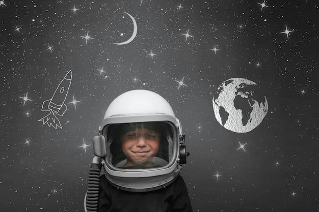 Kleines kind möchte mit einem astronautenhelm im weltraum fliegen