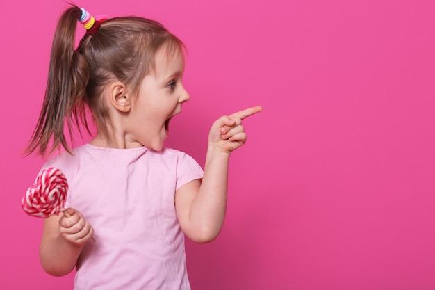 Kleines kind öffnet den mund weit, schaut aufgeregt auf die andere seite und hält den hellen lutscher des herzens. verspieltes fröhliches kleines blondes mädchen verbringt die freizeit glücklich.