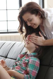 Kleines kind spielt verstecken mit ihrer mutter und schließt die augen