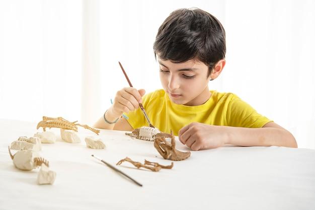 Kleines kind spielt zu hause als paläontologe Premium Fotos