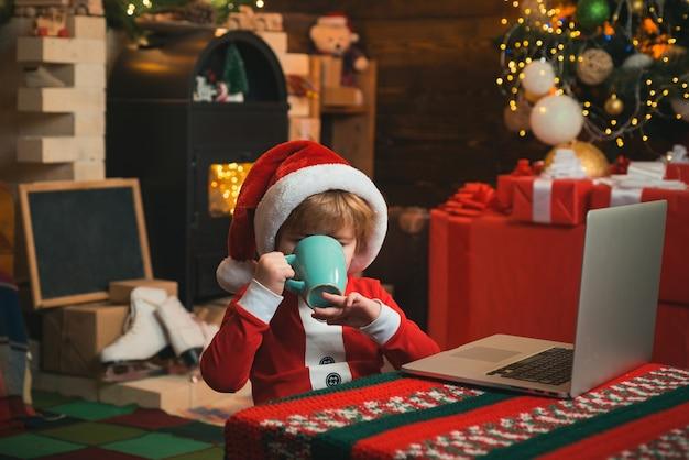 Kleines kind trägt weihnachtsmannkleidung, die an seinem laptop sitzt und heißes weihnachtsgetränk trinkt kaminbac...