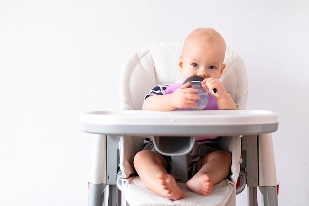 Kleines kind trinkt wasser aus grünem plastikbecher auf hochstuhl