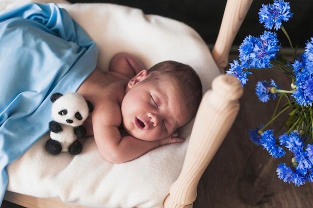Kleines kind unter blauer decke