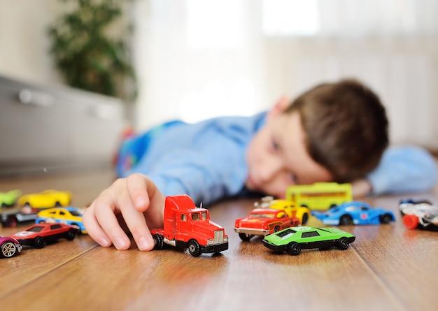 Kleines kind vorschuljunge spielt spielzeugautos
