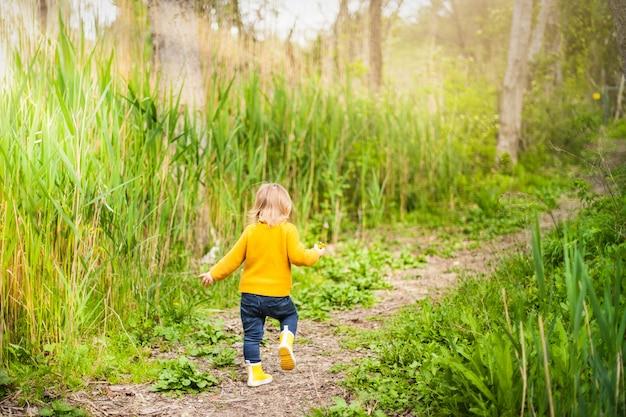 Kleines kind, welches die gelben regenstiefel, gehend entlang einen waldweg im gras trägt