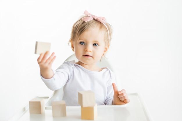 Kleines kind zeigt holzklotz. kindererziehung nach der montessori-methode. umweltfreundliches holzspielzeug. kleinkind lokalisiert auf weißem hintergrund.
