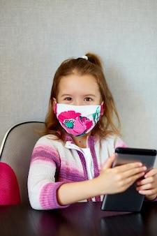 Kleines kind zu hause, trägt eine schutzmaske und spielt auf einem tablet, coronavirus-quarantäne. schule zu hause, online lernen, von zu hause lernen, soziale distanzierung. bleiben sie zu hause konzept.