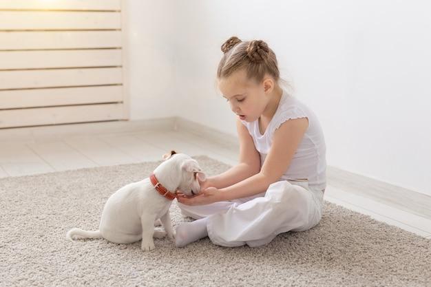 Kleines kindermädchen, das auf dem boden mit niedlichem welpen jack russell terrier sitzt